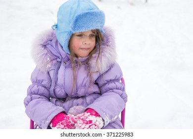 Tired and disheveled walk up five year old girl sitting on a sled