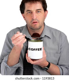 Tired, dishevelled business man eating coffee from the can.