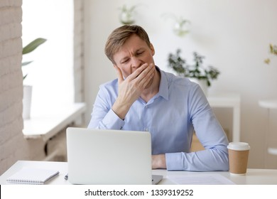 Tired drowsy bored businessman yawning at workplace near laptop, boring work, dead end job, overwork extra after hours, lack of sleep, insomnia consequences, need rest, no energy, Monday