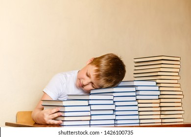 tired eight-year-old boy sleeping on books at the table. children and reading. first-grader