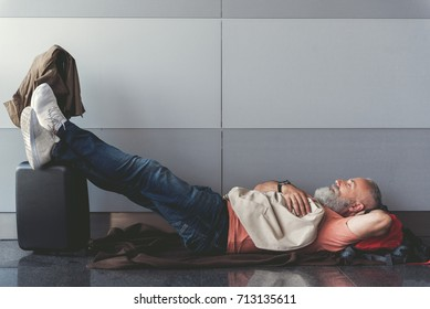 Tired elder man sleeping near wall