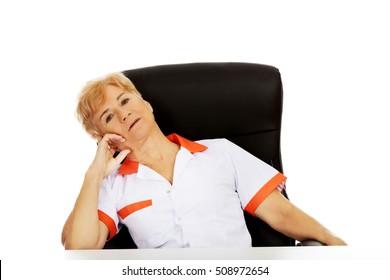 Tired elderly female doctor or nurse sitting behind the desk