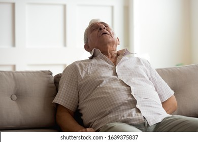 Tired elderly man relax fall asleep on comfortable couch in living room, exhausted mature male take nap daydreaming on cozy sofa at home, suffer from sleep deprivation feel fatigue and exhaustion
