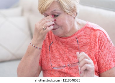 Tired Elderly Person. Senior woman with sinusitis (sinusitis). Woman having nose ache. Lady touching her nose isolated. How to cure sinusitis.