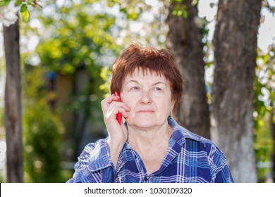 Tired elderly woman at the dacha talking on the cell phone on a spring day.