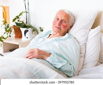 Tired elderly woman laying in bed alone in a nursing home.