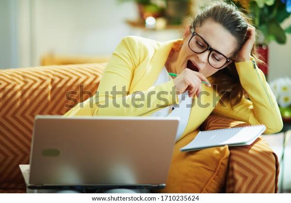 mujer estudiante elegante y cansada con pantalones vaqueros y chaqueta amarilla en la casa moderna en un día soleado estudiar en línea en una laptop.