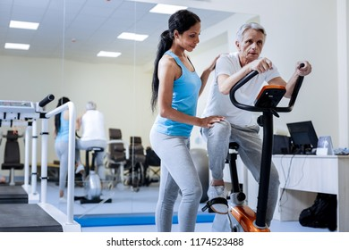 Tired. Enthusiastic active aged man looking exhausted while sitting on the exercise bike in a rehabilitation center with a professional responsible attentive medical worker standing by his side