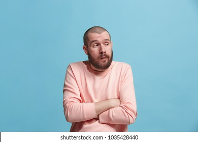I am tired of everything. Bored man. Boring, dull, tedious concept. Young caucasian emotional man. Human emotions, facial expression concept. Studio Isolated on trendy blue background