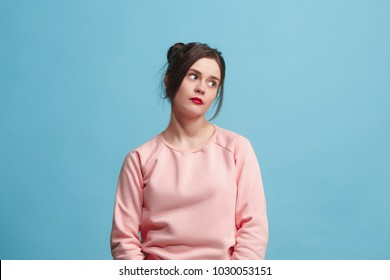 I am tired of everything. Bored woman. Boring, dull, tedious concept. Young pretty caucasian emotional woman. Human emotions, facial expression concept. Studio Isolated on trendy blue background