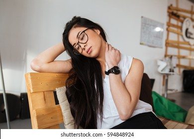 Tired exhausted asian young woman in glasses sitting and relaxing