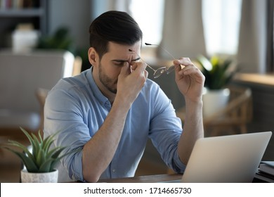 Tired exhausted businessman massaging nose bridge, taking off glasses, feeling eyestrain, sitting at work desk, young man suffering from dry eye syndrome, fatigue after long laptop use