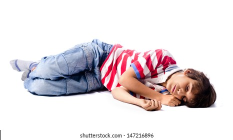 Tired, exhausted child sleeping on the floor, isolated on white background