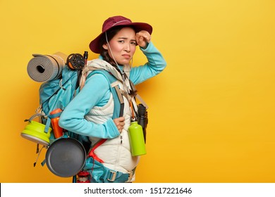 Tired exhausted female tourist walks long distance on foot, looks with dissatisfaction at camera, stands sideways against yellow background, carries backpack with personal stuff. Traveling and tourism
