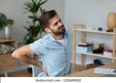 Tired exhausted man feeling pain in back suffering from lower lumbar backache herniated disc after sedentary work, fatigued man rubbing spine muscles sitting in incorrect posture, backpain concept