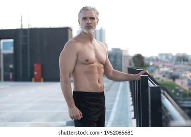 Müde ausgebeuteter Mann mittleren Alters, der sich nach dem Laufen im Freien zurückhält. Praktischer Läufer, der nach Fitness Training eine Pause einlegt