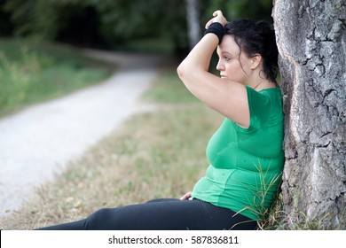 Tired exhausted overweight plus sized woman sitting next to tree