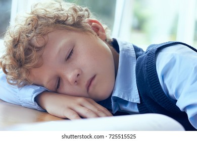 Tired and exhausted primary school student falling asleep while studying.