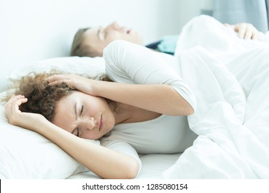 tired exhausted stressed man snoring, portrait of stressful, exhausted man snoring while woman blocking ears on bed in bedroom environment; health, mental care medical concept. adult Couple model