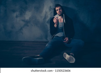 Tired exhausted with stubble bristle in black clothes jeans hipster sitting on floor looking staring at transparent bag with powder in hand wants to take a dose