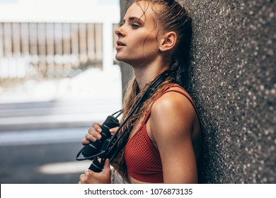 Tired and exhausted woman resting after intense training session. Female with skipping rope leaning to a wall and taking break from physical training.