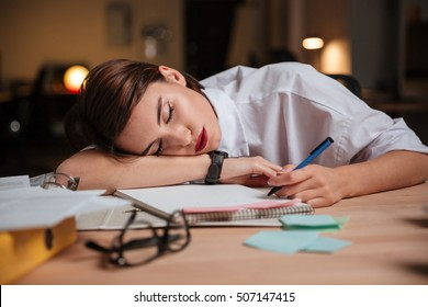 Tired exhausted young businesswoman sleeping at workplace in office