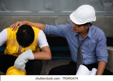Tired and exhausted young foreman cry while Senior engineer manager encourage and cheer up at construction site. Hard working  and bad economy situation forces employee to sign off.