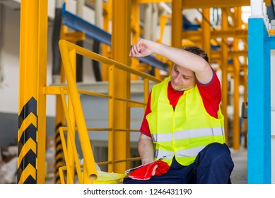 Tired factory worker wipes his sweat and resting after hard work