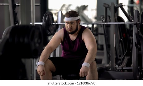 Tired fat man thinking over weight problems, desire to lose weight, gym workout