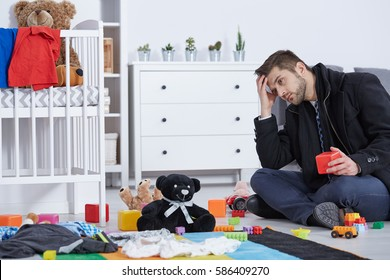 Tired father sitting on floor among baby toys