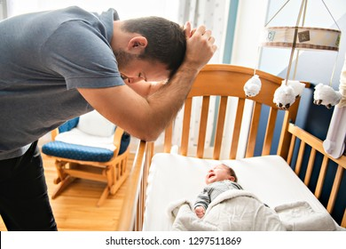 Tired father with Upset Baby Suffering with Post Natal Depression.