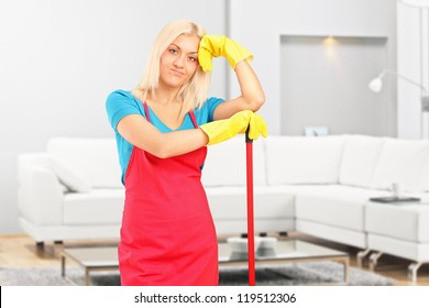 A tired female cleaner resting after cleaning an apartment