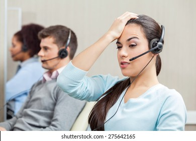 Tired female customer service representative with colleagues in background at call center