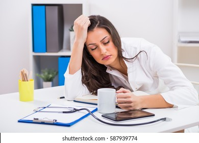 Tired female doctor trying to stay awake with cup of coffee while working at her office.Exhausted female doctor