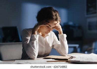 Tired female looking at sketch in notepad while working in the night