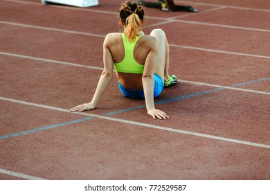 tired female runner sitting on track, finish line sprint