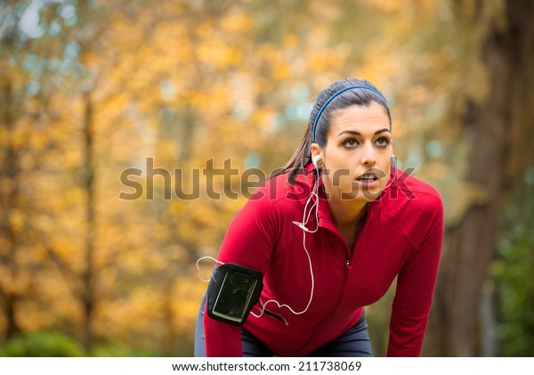 Tired female runner taking a break. Sporty woman breathing and resting on running training in autumn.