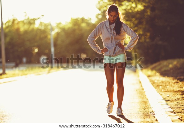 Tired female runner taking a break after  jogging .