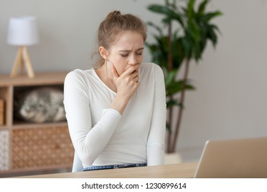 Tired female sitting at home office desk studying, yawning having sleep deprivation, exhausted girl working at laptop, sigh covering mouth feeling sleepy, young woman lack rest, need relax