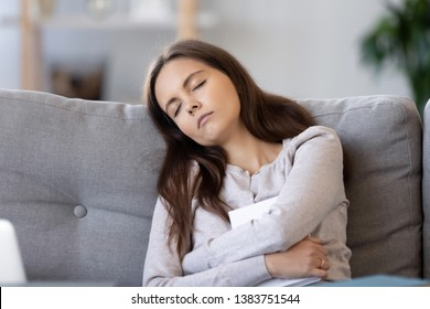 Tired female student fall asleep with textbook in hands on couch during studying preparing for exam, exhausted young woman asleep reading book relaxing on sofa in living room. Fatigue concept
