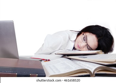 Tired female student sleeping above textbooks with laptop on desk, isolated on white background