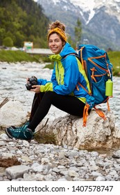 Tired female tourist sits on stones near little stream in mountains, holds professional camera, views photos, wears anorak and comfortable boots, carries heavy rucksack, enjoys camping trip.
