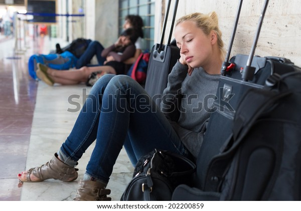 Tired female traveler waiting for departure, resting on the station floor with all her luggage.