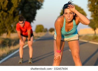 Tired fitness couple of runners sweating and taking a rest during marathon training in country road. Sweaty athletes after running hard.