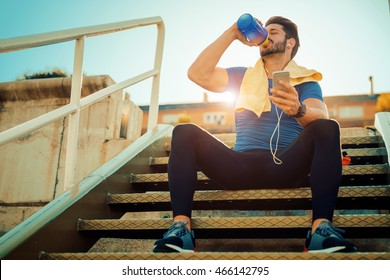 Tired fitness man sweating taking a break listening to music on phone after difficult training.Fitness,sport,training and lifestyle concept.
