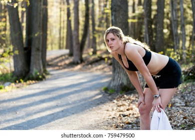 Tired fitness woman in sports bra on nature trail takes break with hands on knees.