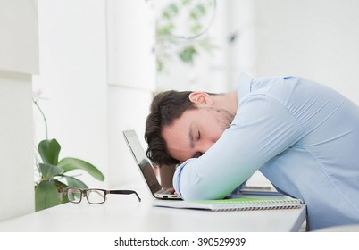 Tired freelance man in blue shirt sleeping on laptop computer while working with bisuness projects in restaurant or cafe.
