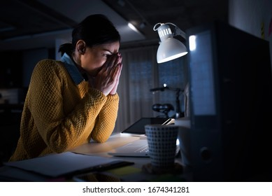 Tired freelancer woman feeling upset having problems with project. Frustrated worried  woman looks at laptop upset by bad news.