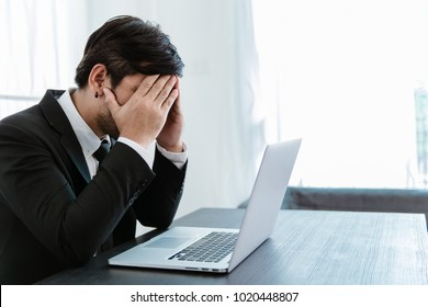 Tired frustrated business people feeling stressed, upset executives sitting near laptop, holding head in hands, worried about business problem failure, depressed by bad news,