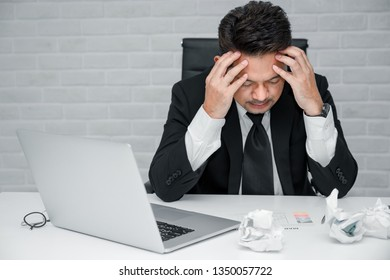 Tired frustrated businessman feeling stressed and worried about business problem failure, upset executives sitting near laptop, holding head in hands
